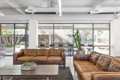 Open office space with comfortable leather couches and large windows.