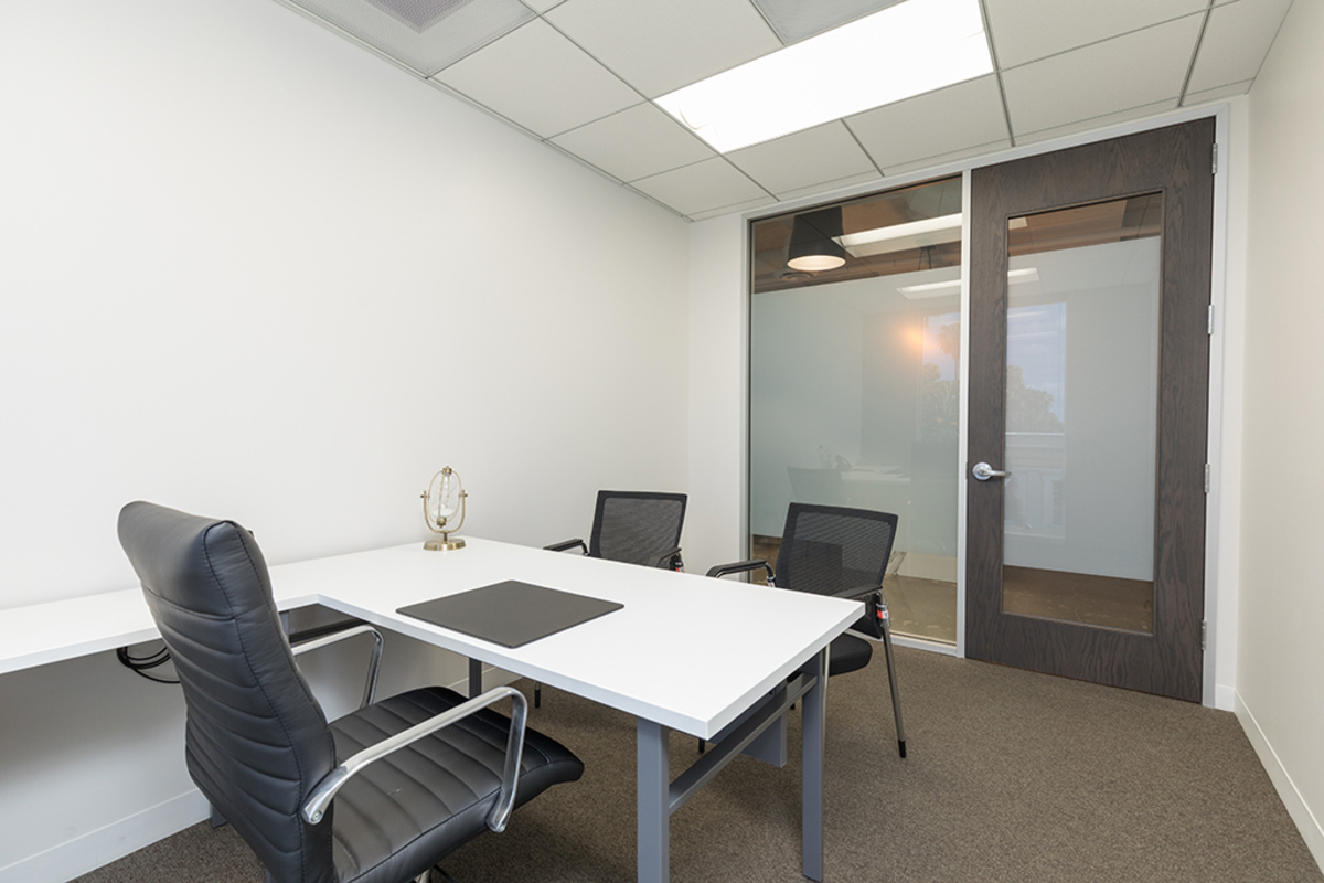 Private office space with large L shaped desk.