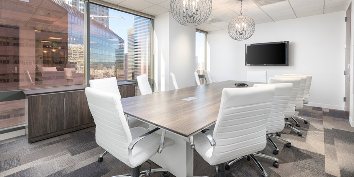 Conference room with large table and white chairs.